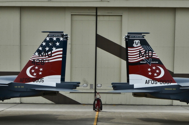 Two Republic of Singapore Air Force F-15SG Strike Eagles are parked to display their new tail flashes outside the Peace Carvin V celebration at Mountain Home Air Force Base, Idaho, May 16, 2014. Mountain Home Air Force Base, Idaho has proven to be the ideal location for the Buccaneers to train on the RSAF's newest fighter platform, as the base controls and maintains almost 7,500 square miles of operational range space complete with emitter sites to simulate opposing forces. Access to airspace and ranges allows for realistic, safe training and testing, while providing flexibility to accommodate preparation for the allied nations – all culminating in world-class instruction. (U.S. Air Force photo by Master Sgt. Kevin Wallace/RELEASED)