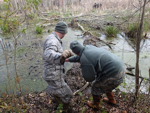Staff Sgt. Tim Baker of the Kentucky Air National Guard's 123rd Civil Engineer Squadron and Master Sgt. Greg Stephens of the 116th Air Control Wing position detonation cord and C4 explosive to blow up unoccupied beaver dams at Robins Air Force Base, Ga., on April 27, 2014. (Courtesy photo)