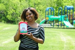 """LaShanda Jones, holds a copy of her first published childrens' book, """"Kele Vorel and Courtney Queen"""" on May 19, 2014, in front of the Joint Base Andrews, Md.,459th Air Refueling Wing playground. Jones, a retired Air Force veteran, is the chief of finance at the wing. (U.S. Air Force photo / Amber J. Russell)"""