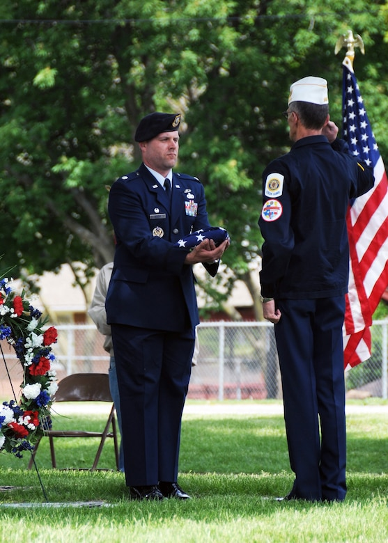 Lt. Col. Christopher Nieman, commander of the 509th Security Forces Squadron, Whiteman Air Force Base, Mo., holds the folded flag as Joe Cochran, Veterans of Foreign Wars Post 2591, salutes during an Armed Forces Day ceremony May 17, 2014, in Sedalia, Mo. Nieman and more than 50 Airmen of the 509th SFS stood alongside family members of 2nd Lt. George A. Whiteman, Sedalia Veterans and cadets, and community members. (U.S. Air National Guard photo by Senior Airman Nathan Dampf/Released)