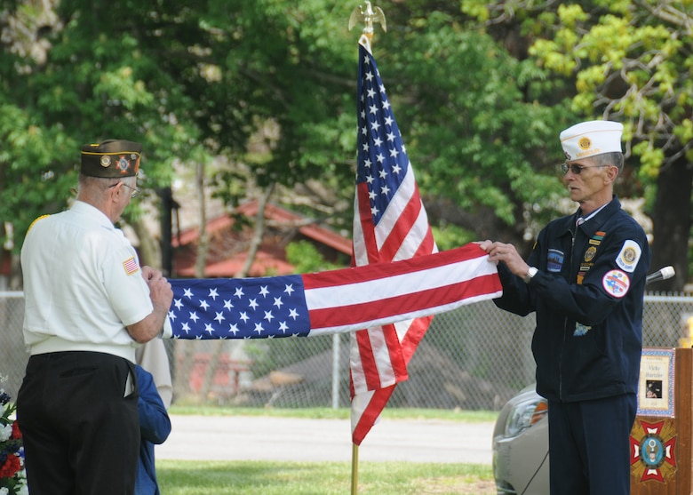 Members of the Sedalia Veterans of Foreign Wars Post 2591 fold the flag that was raised over 2nd Lt. George A. Whiteman's grave during the Armed Forces Day remembrance ceremony May 17, 2014, in Sedalia, Missouri. The veterans raised the flag and provided a three-shot gun salute during the event. (U.S. Air National Guard photo by Senior Airman Nathan Dampf/Released)