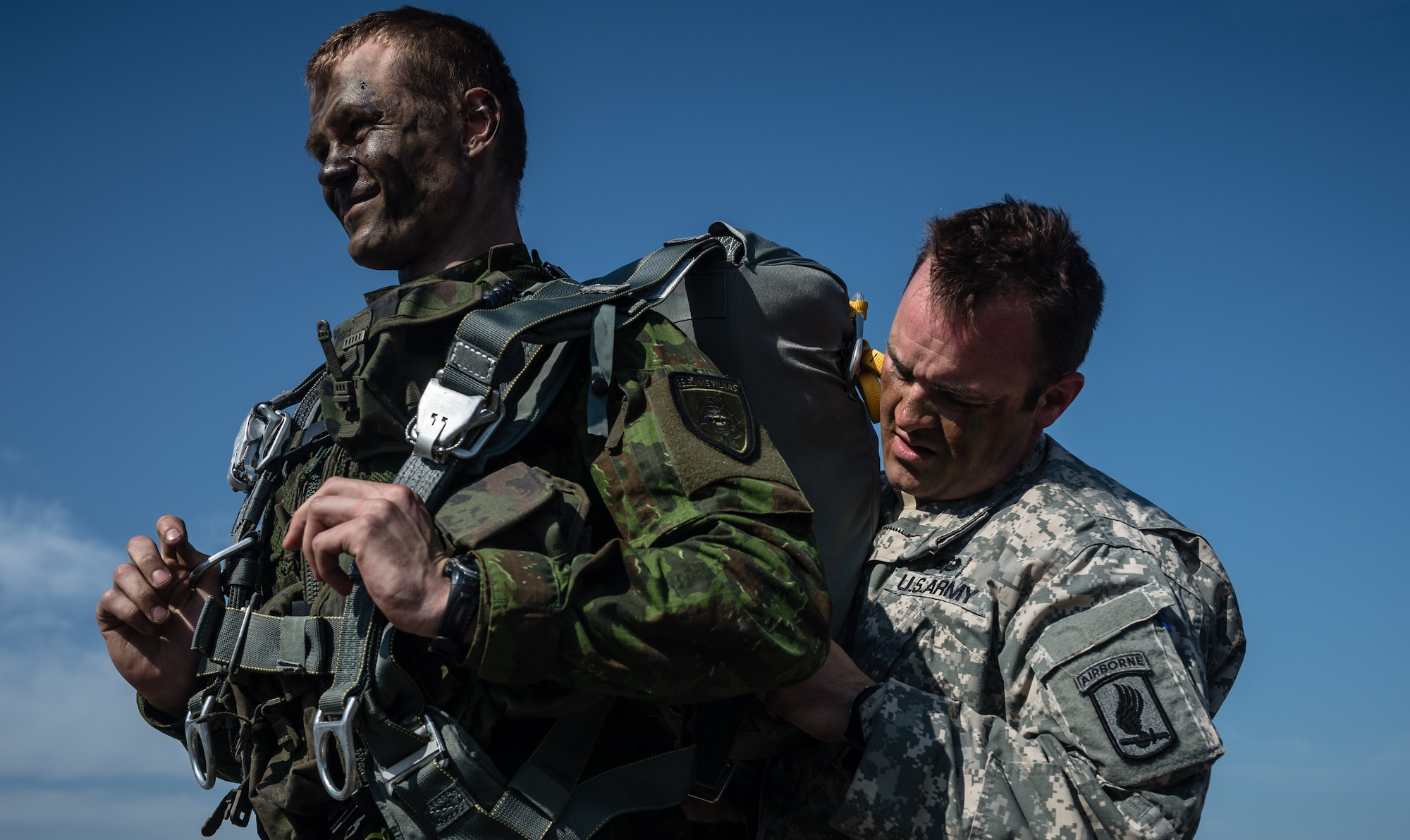 Army Sgt. Zachary McCarter, 1st Battalion 503rd Airborne Infantry Regiment forward observer, helps Lithuanian Land Forces Crpl. Ramūnas Zimblys prepare his parachute at Šiauliai International Airport, Lithuania, May 17, 2014. Pilots and loadmasters from the 37th AS, alongside an 86th Aircraft Maintenance flying crew chief spent four days across three Baltic countries assisting in personnel drops of allied partners and American service members. (U.S. Air Force photo/Airman 1st Class Jordan Castelan)