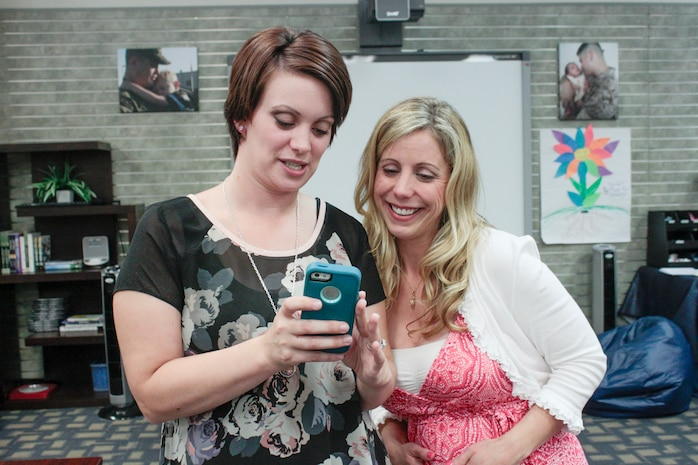 Mollie Gross, a comedienne and speaker, and Jami Lavery, a member of the spouse book club hosted by Marine Corps Family Team Building, look at photos of the book club on Lavery's phone, May 17. Gross offered advice, discussion and jokes for the spouses on the military lifestyle and relying on each other.