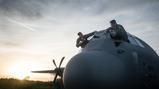 Maj. Jeff Bliss, right, and Capt. Brett Polage, wash off the windows of a C-130J Super Hercules May 17, 2014, at Riga International Airport, Latvia, after air dropping American and Lithuanian paratroopers over Lithuania. Pilots and loadmasters from the 37th Airlift Squadron, alongside an 86th Aircraft Maintenance Squadron flying crew chief, spent four days across three Baltic countries assisting in personnel drops of allied partners and American service members. Bliss and Polage are 37th AS pilots. (U.S. Air Force photo/Airman 1st Class Jordan Castelan)