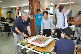 Students at Seoul American Middle School react as Doug Bliss (left), chief of the geotechnical and environmental engineering branch, and Son Ha (center), engineering division design branch chief, test the stability of a student made tower at Seoul American Middle School May 19.