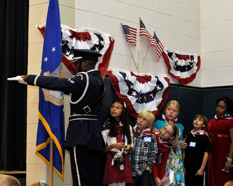 U.S. Air Force Airman First Class Antonio Brooks, Mile High Honor Guard, dresses the U.S. Air Force flag during a Veterans Day salute at Dakota Valley Elementary School in Aurora, Colo. The base honor guard performs final military honors at nearly 570 funerals per year and is the face of the United States Air Force to many families who have lost their loved ones. (U.S. Air Force photo by Tech. Sgt. Wolfram Stumpf/Released)