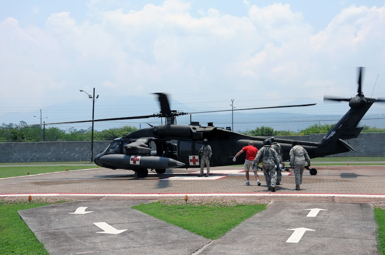 In response to a Honduran government medical evacuation (MEDEVAC) request, personnel from the 1-228th Aviation Regiment and the Joint Task Force-Bravo Medical Element load an automobile accident victim onto a U. S. Army UH-60 Blackhawk MEDEVAC helicopter as they prepare to airlift him to the Hospital Militar in Tegucigalpa, Honduras from the Joint Task Force- Bravo Medical Element's helicopter pad at Soto Cano Air Base, May 13, 2014.  A vehicle traveling west on Honduras Highway CA-5 about 13 miles outside of Comayagua was struck from behind by a tractor trailer truck.  The 18-wheeler subsequently pushed the vehicle into the trailer of another tractor trailer crushing the vehicle.  (Photo by U. S. Air National Guard Capt. Steven Stubbs)