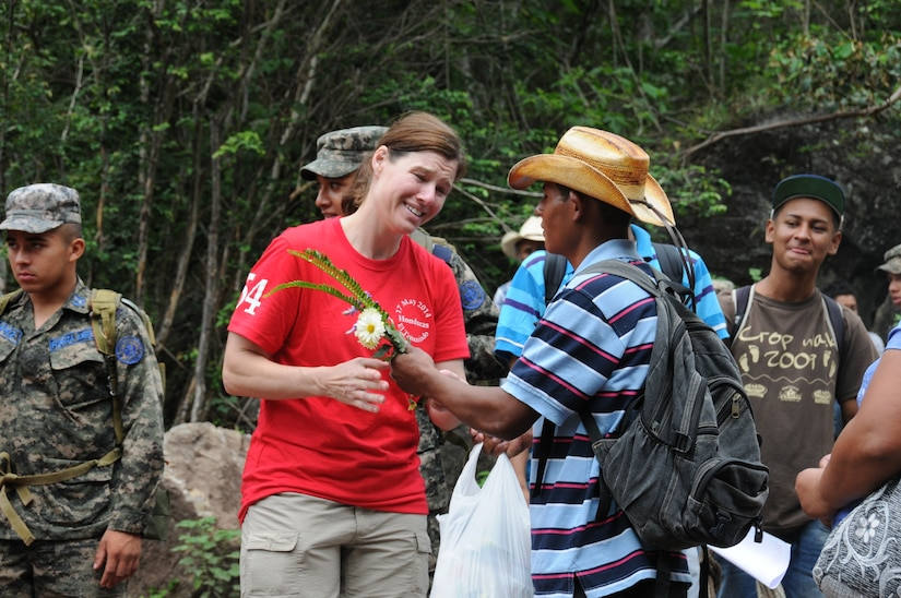 A Honduran man gives U. S. Air National Guard Capt. Sherri Pierce flowers after receiving a bag of food and supplies from her.  More than 120 members of Joint Task Force-Bravo, with the support of Joint Task Force-Bravo's Joint Security Forces and the Honduran military, completed a volunteer seven mile round trip hike to deliver 2,500 pounds of food and supplies to families in need in the mountain village of El Tamarindo outside Comayagua, Honduras, May 17, 2014.  The effort was part of the 54th Joint Task Force-Bravo Chapel Hike, a venerable tradition during which Task Force members donate money to purchase food and supplies and then carry those supplies on a hike through the mountains to deliver them to local, underserviced communities.  (Photo by U. S. Air National Guard Capt. Steven Stubbs)