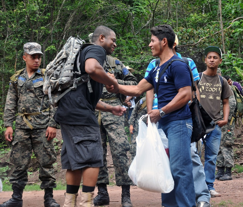 A Honduran man and a Joint Task Force-Bravo member shake hands after receiving a bag of food and supplies.  More than 120 members of Joint Task Force-Bravo, with the support of Joint Task Force-Bravo's Joint Security Forces and the Honduran military, completed a volunteer seven mile round trip hike to deliver 2,500 pounds of food and supplies to families in need in the mountain village of El Tamarindo outside Comayagua, Honduras, May 17, 2014.  The effort was part of the 54th Joint Task Force-Bravo Chapel Hike, a venerable tradition during which Task Force members donate money to purchase food and supplies and then carry those supplies on a hike through the mountains to deliver them to local, underserviced communities.  (Photo by Ana Fonseca)