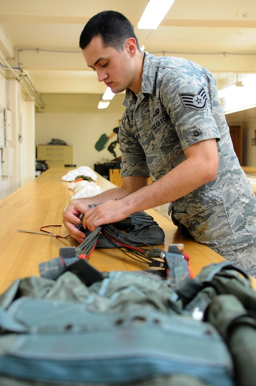 U.S. Air Force Staff Sgt. Travis Crawford, 18th Operations Support Squadron aircrew flight equipment specialist, packs a back-style emergency parachute on Kadena Air Base, Japan, May 21, 2014. The parachute is stored on heavy aircraft such as MC-130P Combat Shadows for emergency evacuation. (U.S. Air Force photo by Senior Airman Marcus Morris)