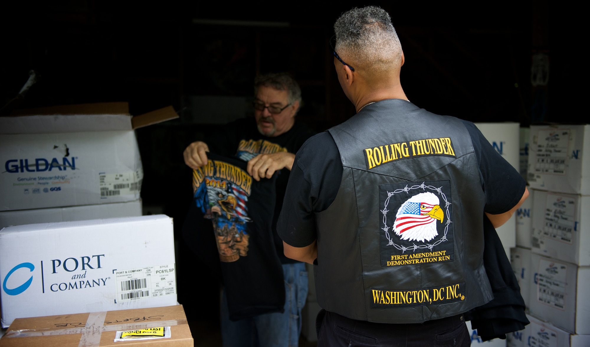 Rob Wilkins, front, and Walt Sides inspect a recent shipment of 2014 souvenir t-shirts for the Rolling Thunder motorcycle demonstration event May 15, 2014 at Sides' farm outside Leesburg, Va. Wilkins is head of Rolling Thunder Magazine and a retired Air Force master sergeant. Sides, a retired Marine first sergeant, original co-founder and executive director of Rolling Thunder, has organized the event since 1988. (U.S. Air Force photo/Senior Airman Alexander W. Riedel)