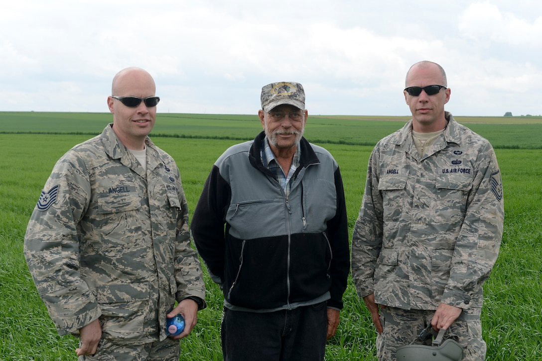 Tech. Sgt. Brian Angell, left, and Master Sgt. Kevin Angell, right, stand with their father, Sam Angell, center, May 8, 2014, during International Jump Week at Alzey landing zone, Germany. Sam Angell flew from Florida to Germany, to see his sons jump together for the first time in both of their careers. (U.S. Air Force photo/Airman 1st Class Michael Stuart)