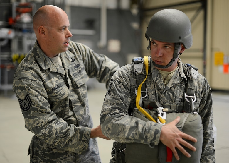 Tech. Sgt. Brian Angell, left, straps in his older brother, Master Sgt. Kevin Angell, into his parachuting equipment  May 8, 2014, at Ramstein Air Base, Germany. Kevin Angell flew in from Korea to jump with his younger brother for the first time in both of their careers. (U.S. Air Force photo/Airman 1st Class Michael Stuart)
