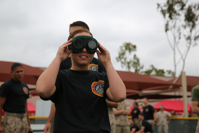 """MARINE CORPS AIR STATION MIRAMAR, Calif. – Lance Cpl. Loryn Graham, weather forecaster with Headquarters and Headquarters Squadron, looks through """"beer goggles"""" in preparation of the """"Dizzy Izzy"""" competition during the Stronger Warrior Field Meet at Marine Corps Air Station Miramar, Calif., May 22. The """"Dizzy Izzy"""" involved putting on """"beer goggles"""", which simulated being intoxicated for those who wore them, and sprinting from one point to another."""