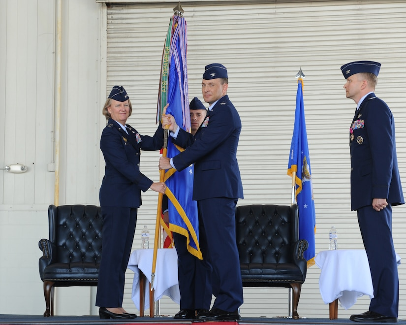 Col. John Lamontagne (right) accepts the 437th Airlift Wing guidon from Maj. Gen. Barbara Faulkenberry, 18th Air Force commander, during the 437th AW change of command ceremony May 22, 2014, in Nose Dock 2 at Joint Base Charleston - Air Base, S.C. Lamontagne took command from Col. Darren Hartford, whose next assignment is 379th Air Expeditionary commander in Al Udeid. (U.S. Air Force photo/Staff Sgt. William O'Brien)