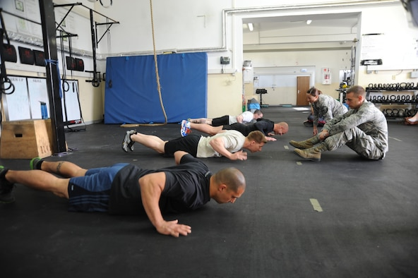 Participants compete in the pushup event during the Wing Staff Agencies Iron Airman competition May 23, 2014, at Spangdahlem Air Base, Germany. Points were earned for every repetition that competitors completed and per yard the ball traveled in the pass, punt, and kick events.  (U.S. Air Force photo by Airman 1st Class Dylan Nuckolls/Released)