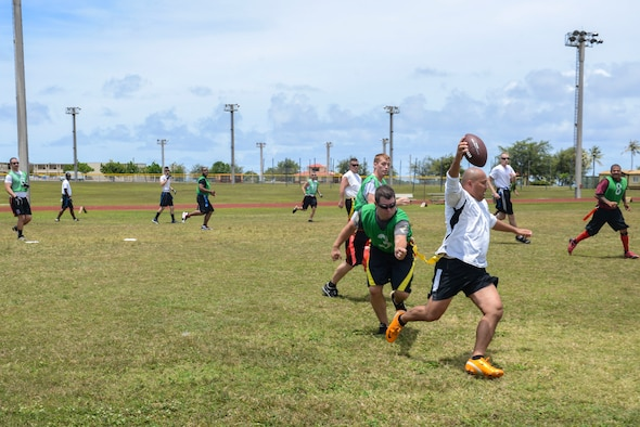 Rich Rollins, 736th Security Forces Squadron, evades a 36th Security Forces Squadron defender during the Battle of the Badges Flag Football Tournament on Andersen Air Force Base, Guam May 13, 2014. The security forces members played an intramural football game as a part of National Police Week along with several other events held that week. (U.S. Air Force photo by Airman 1st Class Adarius Petty/Released)
