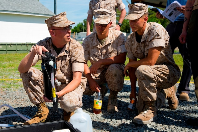 Master Sgt. Kevin Morris (left), project officer for Marine Corps water systems at Marine Corps Systems Command, holds up the filtration system for the small unit water purifier prototype during a demonstration for Marines with 2nd Marine Logistics Group aboard Camp Lejeune, North Carolina May 9. The prototype is designed for platoon-level units and smaller. The system weighs approximately 75 pounds and allows a platoon-size element of Marines to purify 7-10 gallons of water per hour from local water sources.