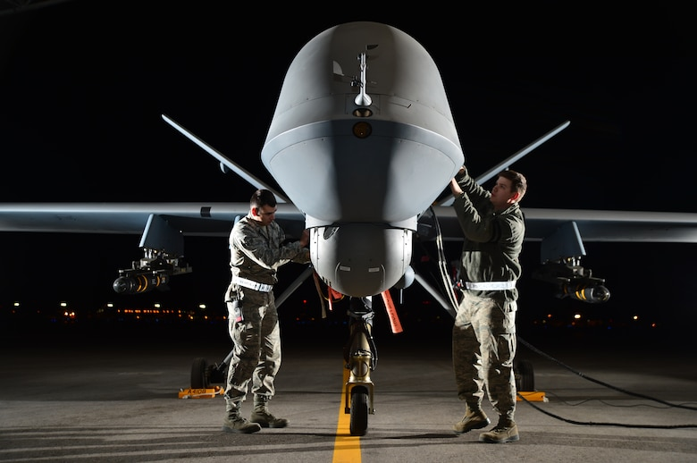 Airman 1st Class Steven and Airman 1st Class Taylor prepare an MQ-9 Reaper for flight during Combat Hammer May 15, 2014,  at Creech Air Force Base, Nev. Fighter, bomber and remotely piloted aircraft units around the Air Force are evaluated four times a year and provided weapons, airspace and targets from Hill AFB, Utah, or Eglin AFB, Fla. Steven and Taylor are MQ-9 crew chiefs with the 432nd Aircraft Maintenance Squadron.  (U.S. Air Force photo/Staff Sgt. N.B.)