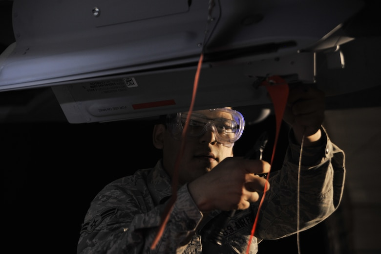 Airman 1st Class Luis safety wires a GBU-12 Paveway II laser-guided bomb onto an MQ-9 Reaper during exercise Combat Hammer May 15, 2014, at Creech Air Force Base, Nev. Fighter, bomber and remotely piloted aircraft units around the Air Force are evaluated four times a year and provided weapons, airspace and targets from Hill AFB, Utah, or Eglin AFB, Fla. Luis is a load crew member with the 432nd Aircraft Maintenance Squadron. (U.S. Air Force photo/Airman 1st Class C.C.)