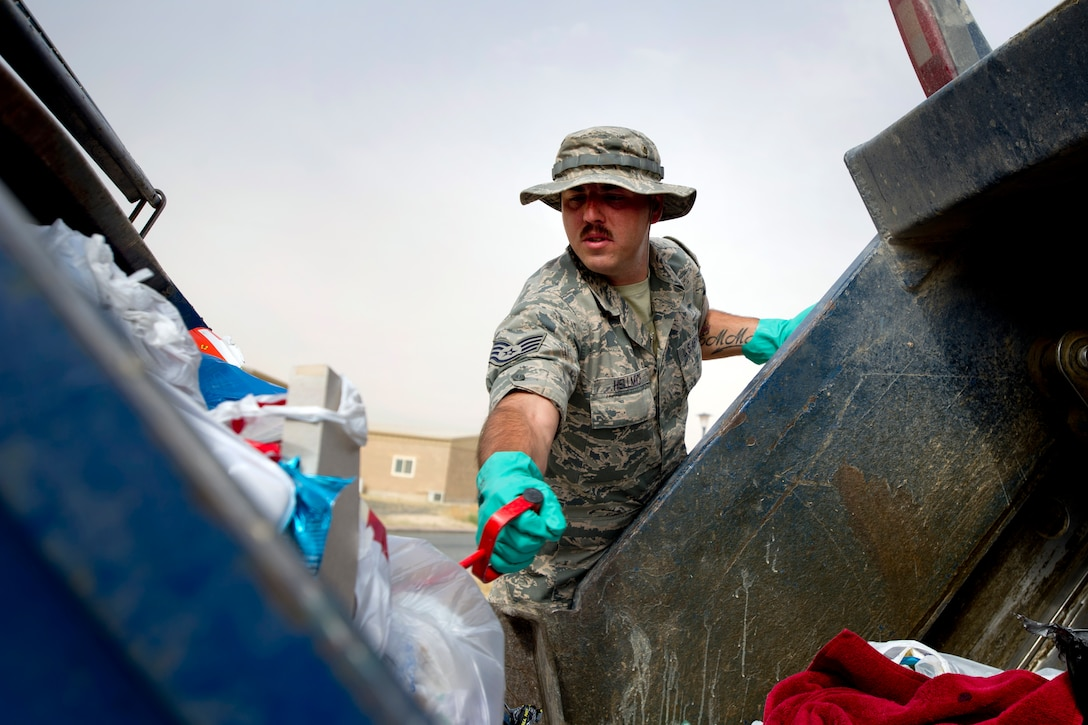 Staff Sgt. Joshua Hellmich sorts through a dumpster of trash looking for OPSEC violations April 18, 2014, in Southwest Asia. Through these inspections and the uniform collection bins, almost 1.5 tons of unserviceable uniform items were collected during the past year and set aside for destruction.  The uniforms were destroyed to ensure they do not end up being utilized improperly if discarded with normal trash.  Hellmich is a member of the force protection flight of the 386th Expeditionary Civil Engineer Squadron. (U.S. Air Force photo/Senior Master Sgt. Burke Baker)