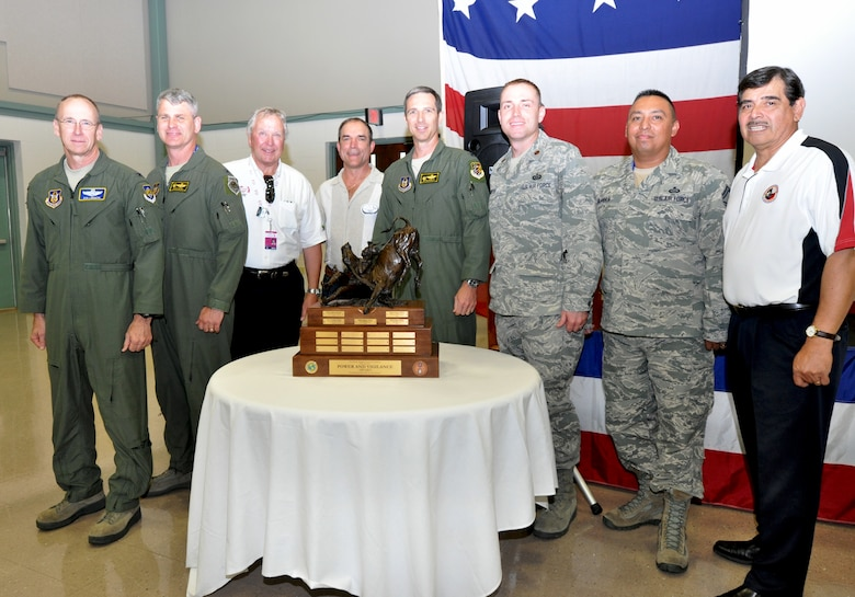 "Colonel Donald Lindberg, 10th Air Force vice commander,  members of the 419th Fighter Wing and Airpower Foundation chairman, Roman Palomares, pose with the Power and Vigilance trophy. The 419th Fighter Wing at Hill Air Force Base, Utah, was recently proclaimed the premier unit within 10th Air Force, winning trophy bragging rights for the year. The Power and Vigilance Award is presented annually to the 10 AF Reserve unit that exhibits the NAF mission as ""the premier provider of affordable, integrated, flexible, and mission-ready Citizen Airmen to execute power and vigilance missions in support of U.S. National Security."" The symbolism of the bronze figure on the award says it all, 'grabbing the bull by the horns'.  They are only the fifth unit to hold this honor. (U.S. Air Force photo/Master Sgt. Julie Briden-Garcia)"