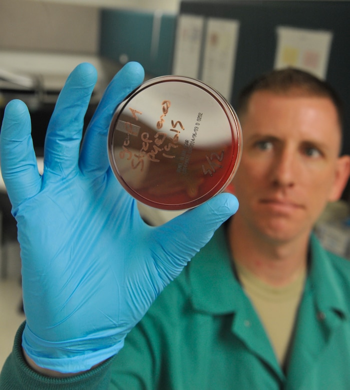 U.S. Air Force Staff Sgt. Jon Ringenoldus, 509th Medical Support Squadron medical laboratory technician, reviews quality control plates at Whiteman Air Force Base, Mo., May 13, 2014. The  plates are reviewed to see if Group A Strep bacteria growth is present. (U.S. Air Force photo by Airman 1st Keenan Berry/Released)