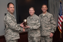 PETERSON AIR FORCE BASE, Colo. -- Col. John Shaw, 21st Space Wing commander, and Chief Master Sgt. Richard Redman, 21st Space Wing command chief, present the Air Force Space Command First Sergeant of the Year trophy May 7 to Master Sgt. Nancy Hinostroza, 21st Civil Engineer Squadron first sergeant. Hinostroza won the award while she was assigned as the 561st Network Operations Squadron first sergeant here. (U.S. Air Force photo/Craig Denton)