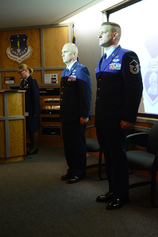 Brig. Gen. Gary L. Ebben, Wisconsin's assistant adjutant general for Air, and Master Sgt. Joshua Johnson, 115th Fighter Wing budget analyst, stand tall during a Purple Heart medal ceremony at the 115 FW in Madison, Wis., May 3, 2014. Johnson was awarded the medal after being thrown from his gunner's seat and injured during a 2005 deployment. (Air National Guard photo by Senior Airman Andrea F. Liechti)