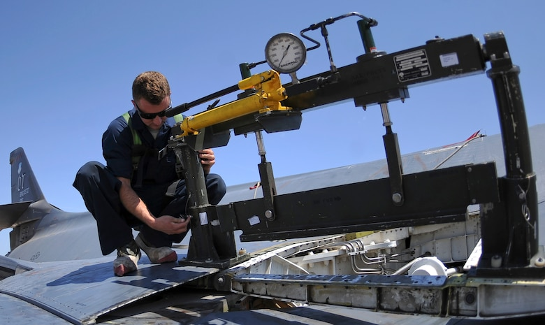 U.S. Air Force Staff Sgt. Billy Trusty Jr., 7th Aircraft Maintenance Squadron B-1B Lancer crew chief, installs a spring panel press on a B-1B Lancer May 20, 2014, at Dyess Air Force Base, Texas. After an in-depth process that included a 200-part questionnaire, background check and an official photo, Trusty was selected for the Presidential Support Team at Andrews Air Force Base, Md. (U.S. Air Force photo by Airman 1st Class Kedesha Pennant/Released)