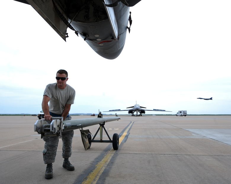 U.S. Air Force Staff Sgt. Billy Trusty Jr., 7th Aircraft Maintenance Squadron B-1B Lancer crew chief, hooks a tow bar to a B-1 May 19, 2014, at Dyess Air Force Base, Texas. Trusty was recently selected for an assignment to the 89th Airlift Wing Presidential Logistics Squadron to perform maintenance on Air Force One at Andrews Air Force Base, Md. (U.S. Air Force photo by Airman 1st Class Kedesha Pennant/Released)