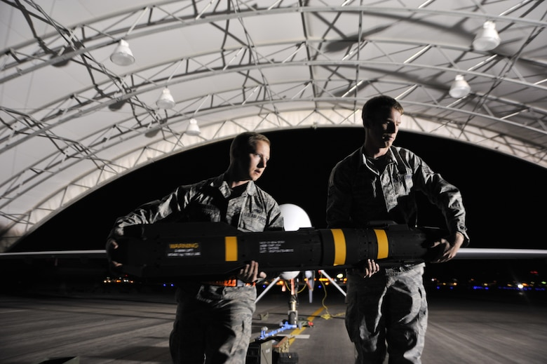 Staff Sgt. Daniel, 432nd Aircraft Maintenance Squadron Tiger Aircraft Maintenance Unit weapons load crew member (left), and Staff Sgt. Nicholas, 432nd AMXS Tiger Aircraft Maintenance Unit weapons load crew chief, transport an AGM-114 Hellfire missile to an MQ-9 Reaper during Combat Hammer May 15, 2014 on Creech Air Force Base, Nev. Combat Hammer is a week-long mission that operationally assesses and evaluates the reliability, maintainability, suitability and accuracy of remotely piloted aircraft munitions. (U.S. Air Force photo by Airman 1st Class C.C./Released)
