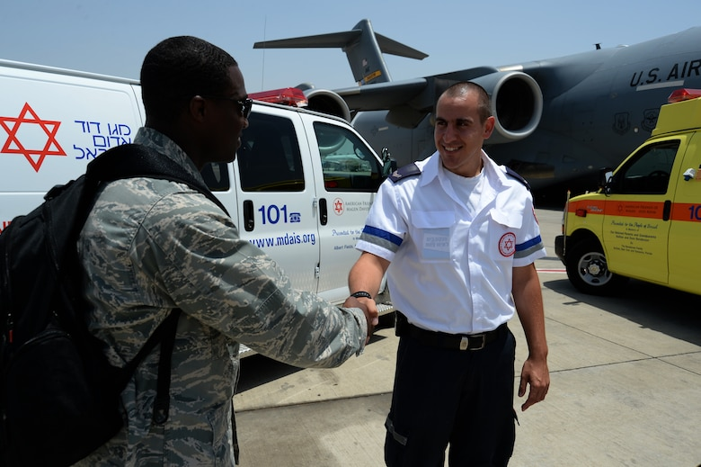 U.S. Air Force Capt. Jason Carter, medical readiness flight commander assigned to the 86th Medical Support Squadron at Ramstein Air Base, Germany, and Rockford, Ill., native, left, shakes the hand of Amit Michael, a Magen David Adom special medic, right, in front of a U.S. Air Force C-17 Globemaster cargo aircraft and two Israeli ambulances after a simulated medical evacuation on the flightline of Ben Gurion International Airport in Tel Aviv, Israel, May 20, 2014 as part of the Juniper Cobra 14 defense training exercise. JC14 is part of a long-standing agreement between U.S. European command and the Israeli Defense Force to hold bilateral training exercises on a regular basis in order to promote and sustain regional stability, and to ensure Israel's qualitative military edge. (U.S. Air Force photo by Staff Sgt. Joe W. McFadden/Released)