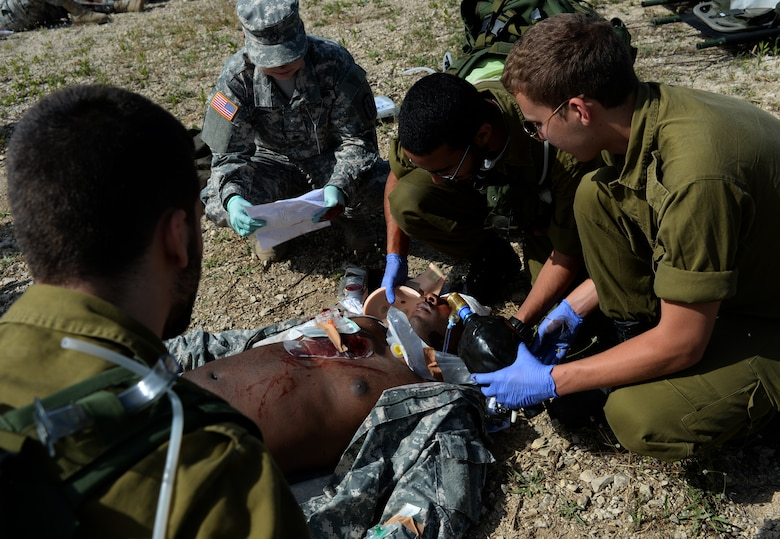 Israeli and U.S. military medics treat the simulated wounds on U.S. Army Staff Sgt. Willie Morgan, a generator mechanic assigned to the 10th Army and Missile Defense Command at Kaiserslautern, Germany, and Atlanta native, during a simulated medical evacuation as part of the Juniper Cobra 14 defense training exercise at Hatzor Air Base, Israel, May 20, 2014. Approximately 2,000 U.S. service members and civilians stationed in Europe and the United States traveled to Israel to participate in JC14 as a training audience or exercise evaluators.  (U.S. Air Force photo by Staff Sgt. Joe W. McFadden/Released)