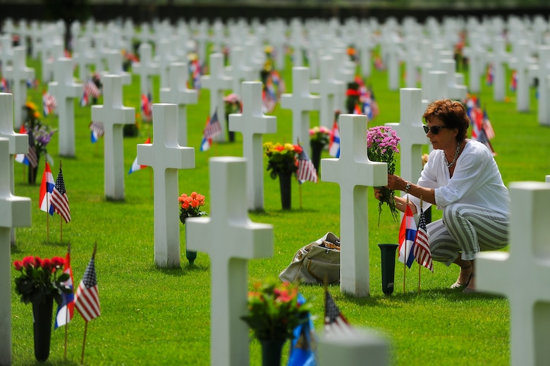 A spectator plants flowers on a headstone at the Netherlands American Cemetery prior to the start of a Memorial Day ceremony May 25, 2014, Margraten, Netherlands. Dutch families can adopt a gravesite and maintain it as a way of showing respect for the actions of the fallen service member. (U.S. Air Force photo by Senior Airman Rusty Frank/Released)