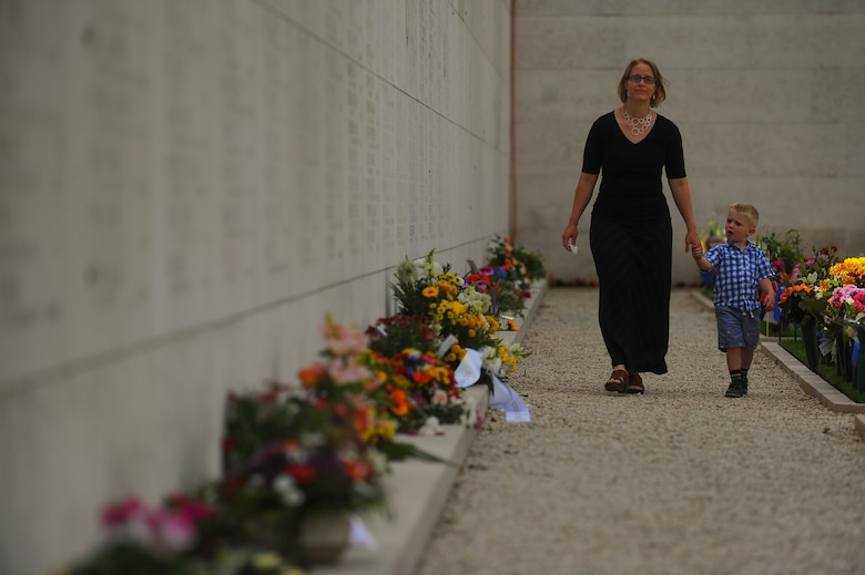 A mother and her child walk past the Wall of the Missing at the Netherlands American Cemetery prior to a Memorial Day ceremony May 25, 2014, Margraten, Netherlands. More than 1,000 names mostly from Operation Market Garden and the Battle of the Bulge are marked on the wall. (U.S. Air Force photo by Senior Airman Rusty Frank/Released)