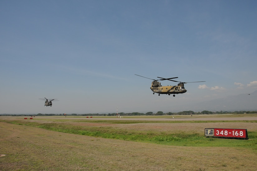 """Two CH-47D Chinooks take off from Soto Cano Air Base, Honduras for the last time, May 28, 2014.  The two Chinooks attached to the 1-228th Aviation Regiment are slated to be replaced with the newer CH-47F model.  One of the helicopterss, affectionately known as """"638"""", is the oldest active Chinook in the U. S. Army's inventory having flown in the Vietnam War.  (Photo by U. S. Air National Guard Capt. Steven Stubbs)"""