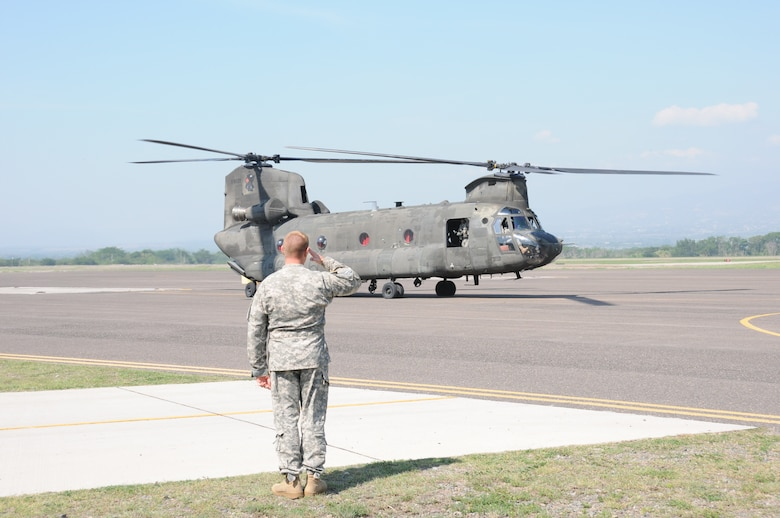 """U. S. Army Lt. Col. Ernest Irvin, 1-228th Aviation Regiment commander, salutes as a CH-47D Chinook prepares to take off from Soto Cano Air Base, Honduras for the last time, May 28, 2014.  Two Chinooks are slated to be replaced with the newer CH-47F model.  One of the helicopterss, affectionately known as """"638"""", is the oldest active Chinook in the U. S. Army's inventory having flown in the Vietnam War.  (Photo by U. S. Air National Guard Capt. Steven Stubbs)"""