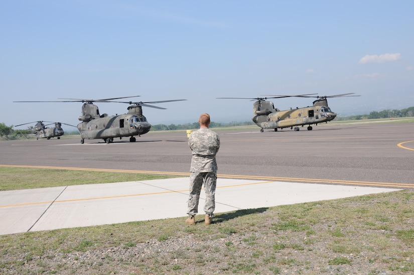 """U. S. Army Lt. Col. Ernest Irvin, 1-228th Aviation Regiment commander, watches as two CH-47D Chinooks prepare to take off from Soto Cano Air Base, Honduras for the last time, May 28, 2014.  The Chinooks are slated to be replaced with the newer CH-47F model.  One of the helicopterss, affectionately known as """"638"""", is the oldest active Chinook in the U. S. Army's inventory having flown in the Vietnam War.  (Photo by U. S. Air National Guard Capt. Steven Stubbs)"""