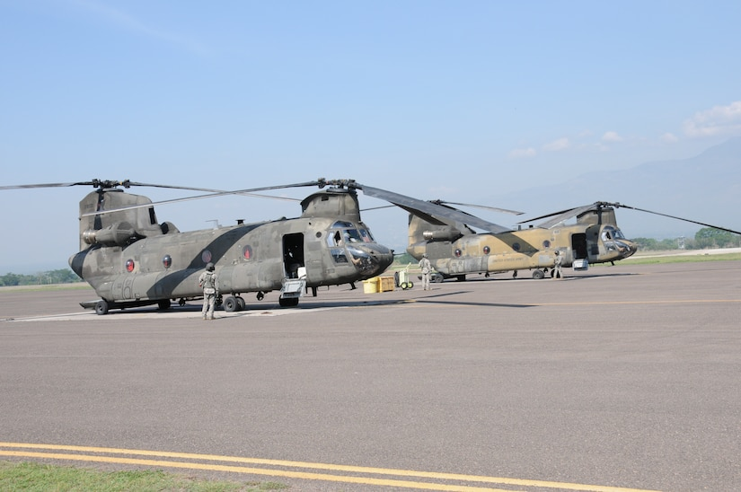 """Two CH-47D Chinook crews perform pre-flight checks before departing Soto Cano Air Base, Honduras for the last time, May 28, 2014.  Two Chinooks attached to the 1-228th Aviation Regiment are slated to be replaced with the newer CH-47F model.  One of the helicopterss, affectionately known as """"638"""", is the oldest active Chinook in the U. S. Army's inventory having flown in the Vietnam War.  (Photo by U. S. Air National Guard Capt. Steven Stubbs)"""