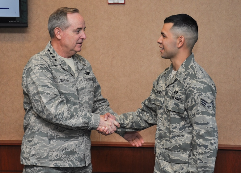 Air Force Chief of Staff Gen. Mark A. Welsh III coins Senior Airman Jose Sanchez, 460th Space Wing legal office, during a visit May 27, 2014, to Buckley Air Force Base, Colo. Welsh's trip to Buckley included mission briefings, Airmen recognition and a chance for the base to meet the Air Force's top officer. (U.S. Air Force photo by 2nd Lt. Trevor Zakrzewski/Released)