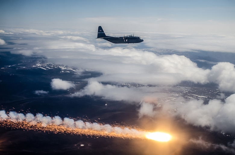 A Kentucky Air National Guard C-130 Hercules flies in formation as another C-130 deploys flare countermeasures in the skies over Alaska during exercise Red Flag-Alaska on May 22, 2014. Aircrews from Kentucky's 165th Airlift squadron received intensive combat training during the exercise, which ran from May 7 to 23. (U.S. Air National Guard photo by Master Sgt. Phil Speck)