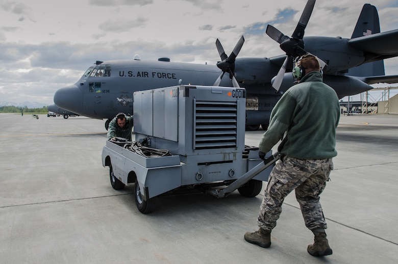 Staff Sgt. Dustin Pennington, an electric environmental craftsman from the Kentucky Air National Guard's 123rd Maintenance Squadron, and Tech. Sgt. Christopher Julian, crew chief for Kentucky's 123rd Aircraft Maintenance Squadron, move a power generator prior to the launch of a Kentucky Air Guard C-130 Hercules at Joint Base Elmendorf-Richardson, Alaska, on May 19, 2014. More than 100 Kentucky Airmen participated in exercise Red Flag-Alaska from May 7 to 23. (U.S. Air National Guard photo by Master Sgt. Phil Speck)