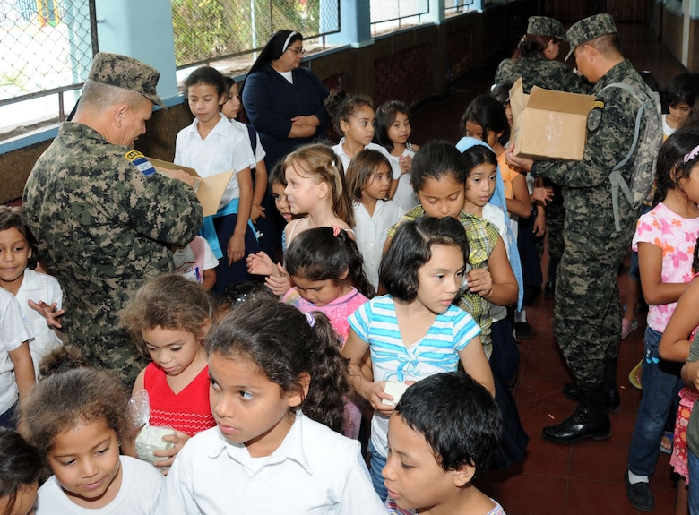 Personnel from the Honduran 21st Military Police Battalion hand out soap kits to the children of the Hogar del Nino school.  Joint Task Force-Bravo, non-government organizations Clean the World, Bridge Ministries and Kick for Nick Foundation, the Honduran 21st Military Police Battalion and the Honduran National Police formed a partnership to distribute soap kits, backpacks with school supplies, tooth brushes and tooth paste, soccer balls and uniforms to students at eight Tegucigalpa, Honduras schools in a two-day event, May 20-21, 2014.  The group handed out over 4,200 soap kits, 600 backpacks, 150 tooth brushes and tooth paste, and 50 soccer balls.  (Photo by U. S. Air National Guard Capt. Steven Stubbs)