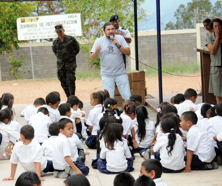 Trifilio Villela from Bride Ministries talks to children of the Policarpo Bonilla school about the improtance of proper hygiene.  Joint Task Force-Bravo, non-government organizations Clean the World, Bridge Ministries and Kick for Nick Foundation, the Honduran 21st Military Police Battalion and the Honduran National Police formed a partnership to distribute soap kits, backpacks with school supplies, tooth brushes and tooth paste, soccer balls and uniforms to students at eight Tegucigalpa, Honduras schools in a two-day event, May 20-21, 2014.  The group handed out over 4,200 soap kits, 600 backpacks, 150 tooth brushes and tooth paste, and 50 soccer balls.  (Photo by U. S. Air National Guard Capt. Steven Stubbs)