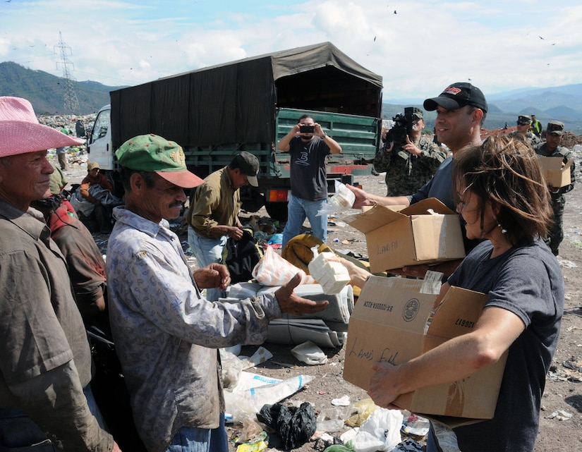 U. S. Army Lt. Col Frank Melgarejo, Joint Task Force-Bravo operations officer and Sandi Burges, Bridge Ministries founder, hand out soap kits to people at the Comayaguela Landfill.  Joint Task Force-Bravo, non-government organizations Clean the World, Bridge Ministries and Kick for Nick Foundation, the Honduran 21st Military Police Battalion and the Honduran National Police formed a partnership to distribute soap kits, backpacks with school supplies, tooth brushes and tooth paste, soccer balls and uniforms to students at eight Tegucigalpa, Honduras schools in a two-day event, May 20-21, 2014.  The group handed out over 4,200 soap kits, 600 backpacks, 150 tooth brushes and tooth paste, and 50 soccer balls.  (Photo by U. S. Air National Guard Capt. Steven Stubbs).
