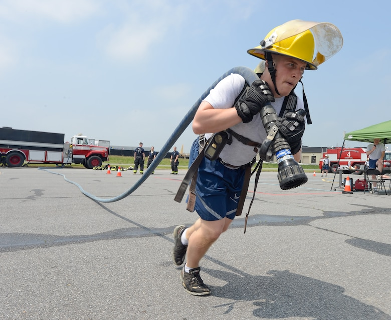 A participant in the Firefighter's Challenge drags a fire hose out to full length during the 2014 Wingman Day at Eagles Nest Park on May 22, 2014, at Dover Air Force Base, Del. Ten, four person teams participated in the fast-paced event while wearing protective equipment.