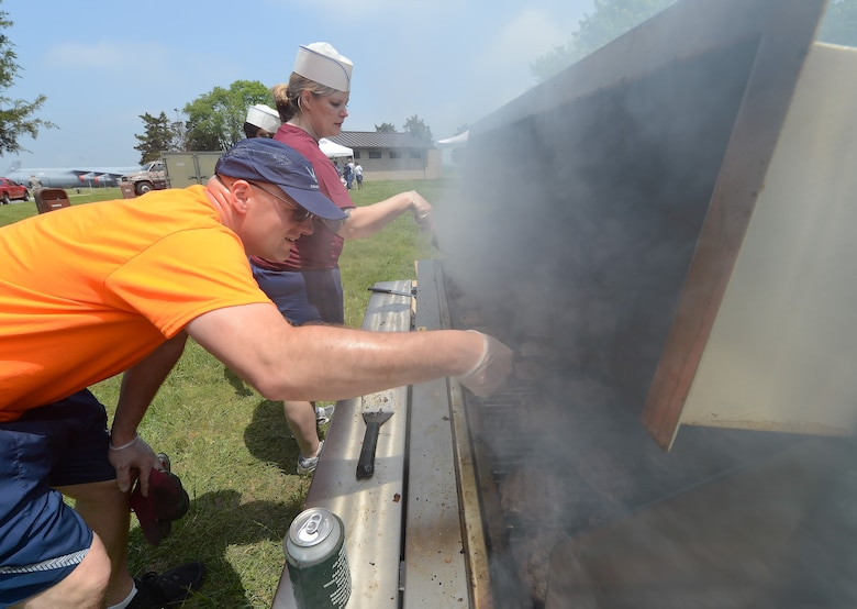 Master Sgt. Benjamin Fay, foreground, 9th Airlift Squadron, and Technical Sgt. Crystal Mallory, 436th Medical Group, peer in to smoke billowing from a grill while cooking hamburgers during the 2014 Wingman Day at Eagles Nest Park on May 22, 2014, at Dover Air Force Base, Del. Two grills were used to cook enough food to feed attendees. (U.S. Air Force photo/Greg L. Davis)