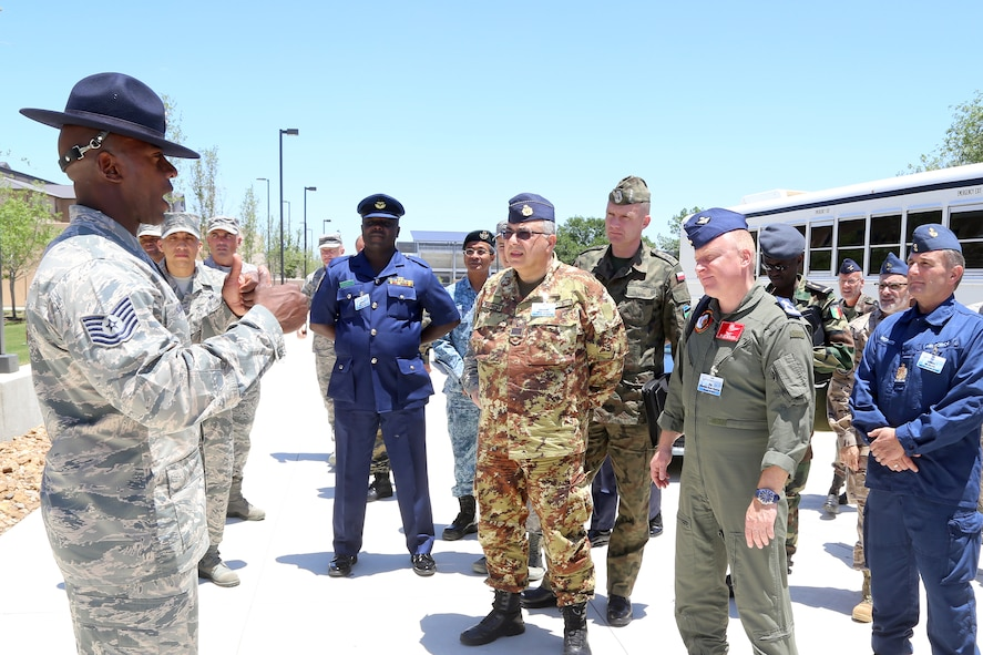 A Military Training Instructor speaks with senior enlisted leaders from the air forces of 24 countries as they tour basic military training facilities at Joint Base San Antonio-Lackland, Texas. Chief Master Sgt. of the Air Force James Cody hosted an international senior enlisted leader summit May 13-16. (U.S. Air Force photo by Joshua Rodriguez)
