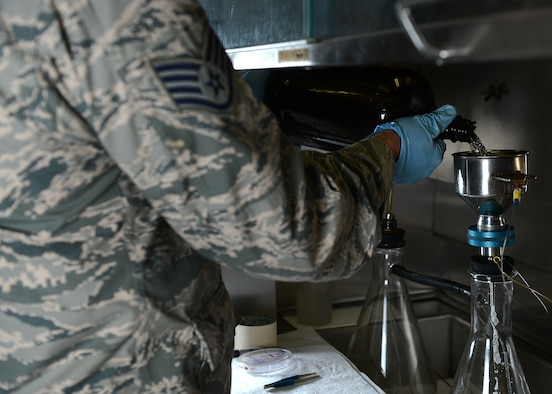 U.S. Air Force Staff Sgt. Mark Harschfeld, 52nd Logistics Readiness Squadron NCO in charge of the fuels laboratory and Helena, Mont., native, pours JP-8 fuel into a filtering flask at Spangdahlem Air Base, Germany, May 23, 2014. Laboratory technicians perform approximately 20 tests daily to ensure top quality of fuel. (U.S. Air Force photo by Airman 1st Class Kyle Gese/Released)